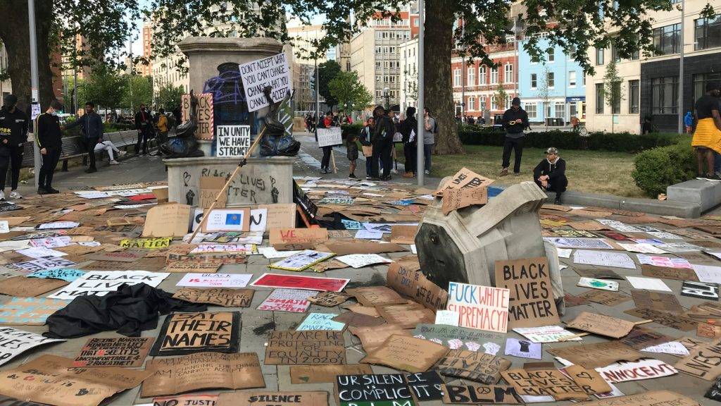 Black Lives Matter placards surround the empty plinth in Bristol, they have been left as reminders and memorials for the protests. People are gathered at the edges, paying their respects.